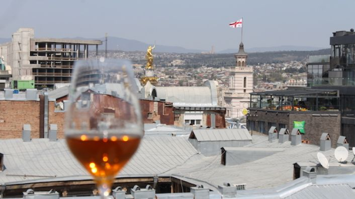 Tblisi rooftops with a glass of orange wine